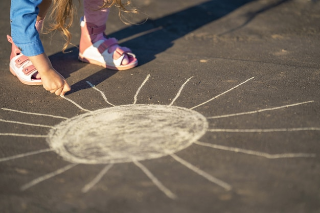 Close-up on child drawing with colored chalk on asphalt