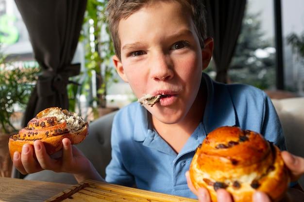 Chiuda sul bambino che mangia il dessert