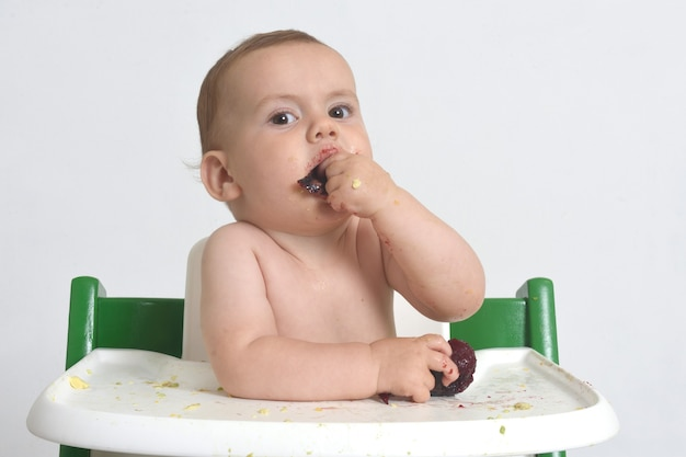 Close-up of a child eating plum on white background