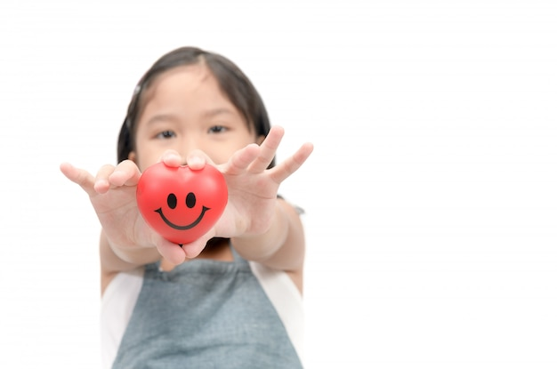 Close up of child hands giving  smile red heart