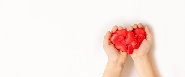 Close up of child hands holding red heart on white background