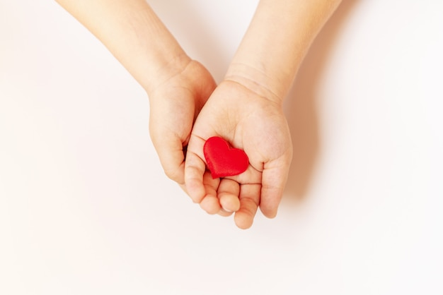 Close up of child hands holding red hearton white background - people, love, charity and family concept