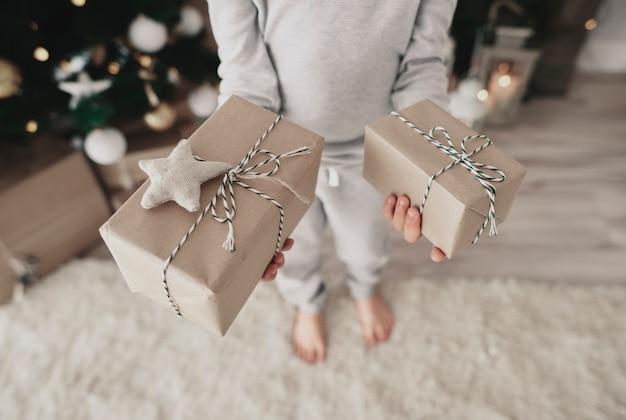 Chiuda in su del bambino che tiene i regali