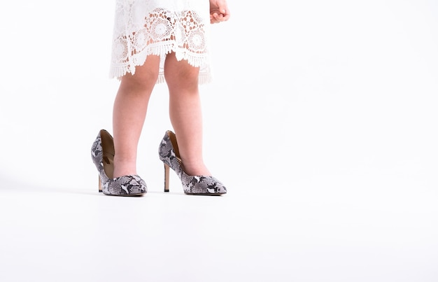 Close up of a child legs in her mother shoes with heels on a white wall