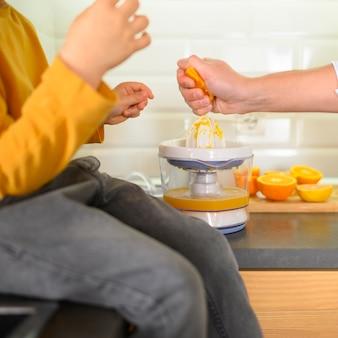 Close-up child and parent making orange juice