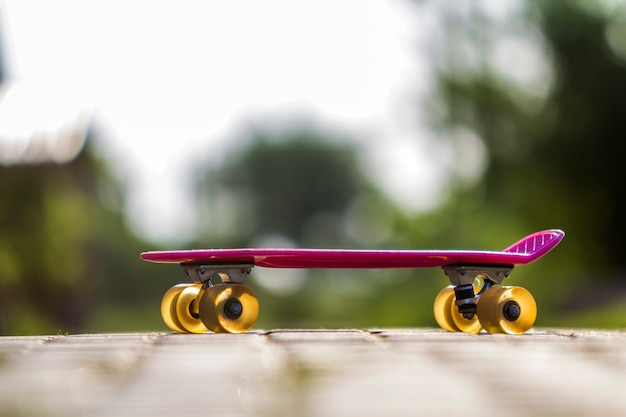 Close-up of child plastic pink skateboard isolated on pavement against bright white and green blurred bokeh scene. sport, recreation, fun and plays concept.