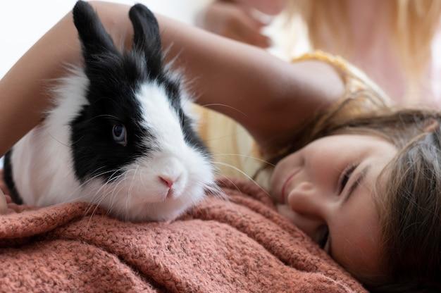 Primo piano sul bambino che gioca con il coniglio domestico