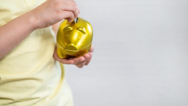 Close-up of child putting coins in piggy bank