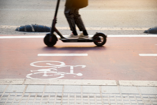 Close-up of a child riding kick scooter on cycle lane