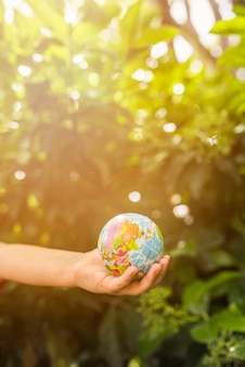 Close-up of child's hand holding globe ball in front of green plant in the sunlight