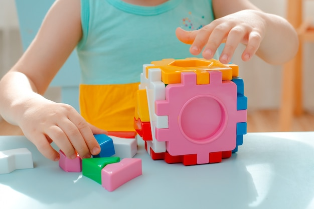 Close-up of the child's hands collect puzzle sorter. cube with inserted geometric shapes and colored plastic blocks.