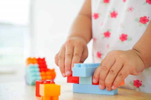 Close up of child's hands playing with colorful connector toys at the table. educational toys for preschool and kindergarten child.
