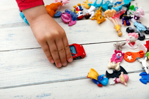 Close up of child's hands playing with colorful plastic bricks at the table.