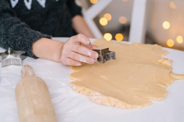 Руки ребенка конца-вверх подготавливая печенья используя резцы печенья.