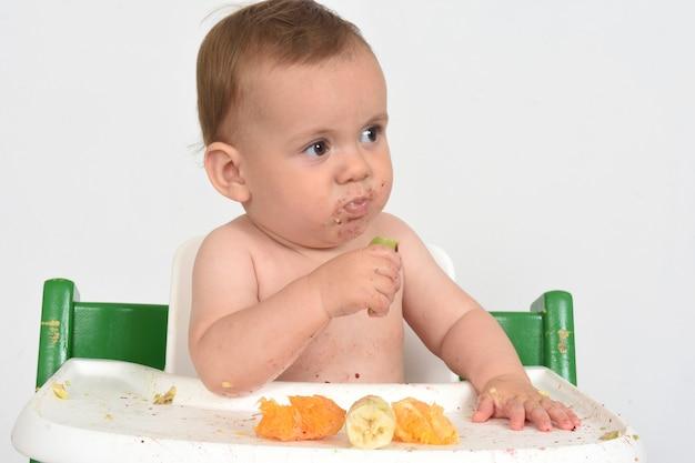Закройте вверх ребенка, который ест фрукты в стульчике для кормления на белом фоне