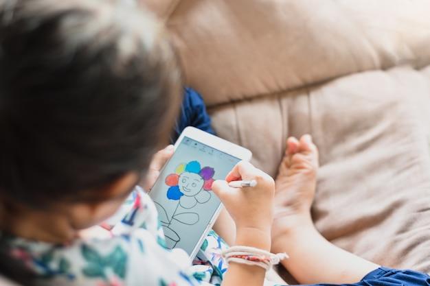 子供たちをクローズアップ小さな女の子は、技術で学習と開発のスマートフォンで描いています