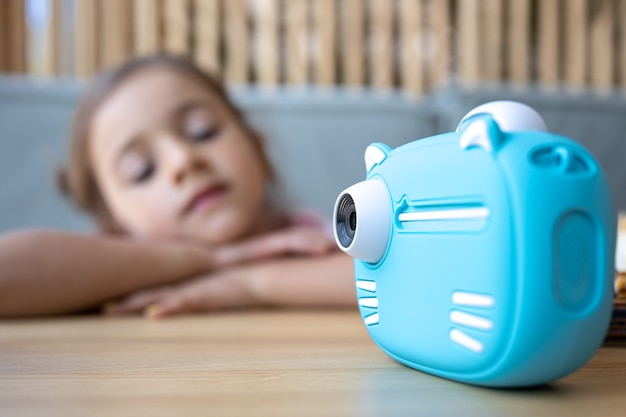 Close-up of children's blue toy camera for instant photo printing.
