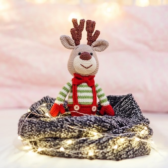 Close up children toy amigurumi deer in striped sweater and stylish red butterfly tie near christmas lights on the pink .