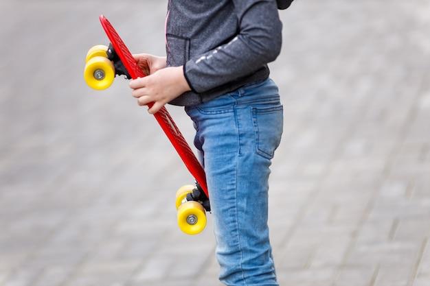 クローズ アップ子供の手は、夏に赤いスケート ボードを保持しています。