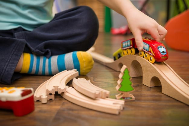 Close up on childs hands with toy train and railway in his room