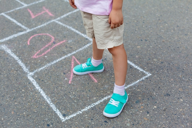 Close-up of childs legs and classics painted on asphalt. little girl playing hopscotch game on playground outside on a sunny day.