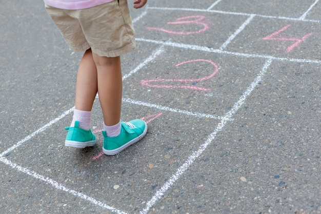 Close-up of childs legs and classics painted on asphalt.