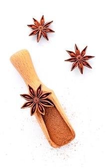 흰색 배경에 분리된 나무 국자에 중국 스타 아니스를 닫습니다. 말린 스타 아니스 향신료 과일은 위쪽 전망과 복사 공간을 제공합니다.
