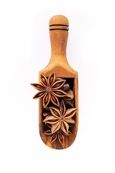 흰색 배경에 분리된 나무 국자에 중국 스타 아니스를 닫습니다. 말린 스타 아니스 향신료 과일 평면도.
