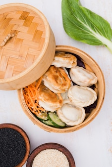Close-up of chinese steamed dumplings with salad in steamer basket with black and white sesame seeds