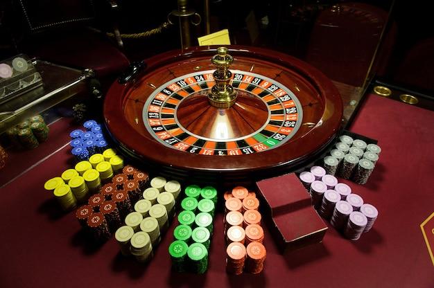 빨간 테이블에 있는 카지노에서 클로즈업 칩과 룰렛