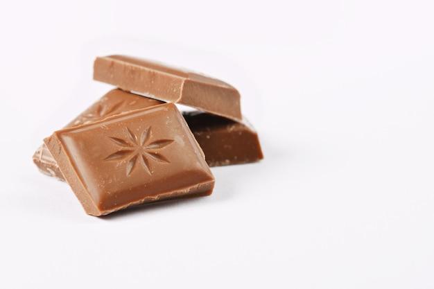 Chiuda in su una barra di cioccolato isolata su priorità bassa bianca.