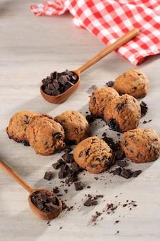 灰色の木製テーブルのコピースペースでチョコレートチップクッキーの背景を閉じます。子供のための自家製食品/スナック