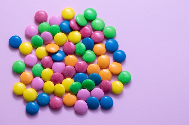 Close up of chocolate egg and candy drops on pink table