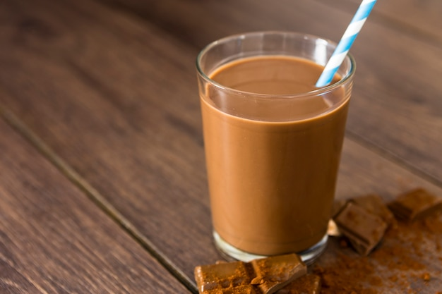 Close-up of chocolate milkshake with straw and cocoa