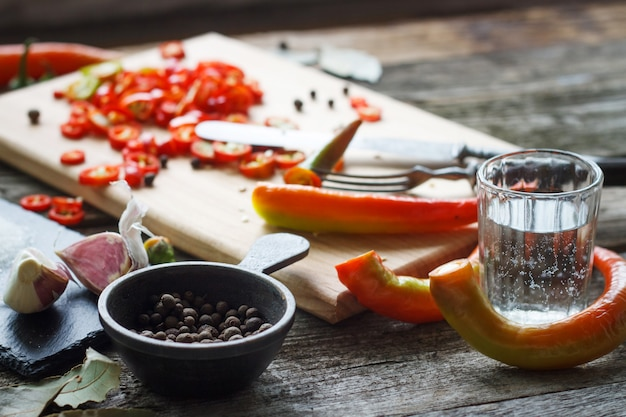 Close-up of chopped hot chili peppers and heaps of salt, sugar, garlic, allspice, bay leaf on an old wooden surface