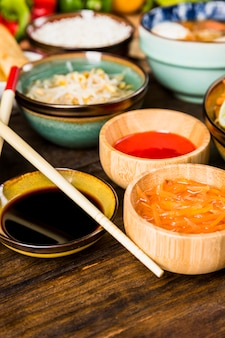 Close-up of chopstick with soya; red chili sauces and grated carrots in wooden bowl on desk