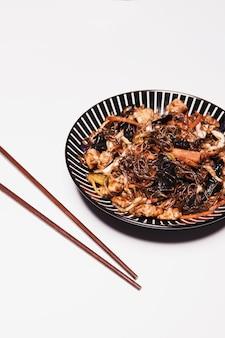 Крупным планом палочки для еды и азиатской кухни на белом