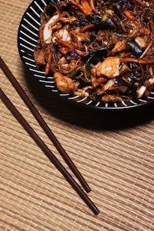 Close-up chopsticks near Asian food