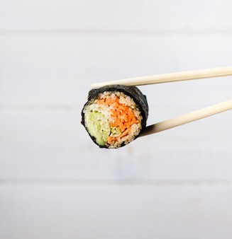 Close-up chopsticks and sushi roll with blurred background