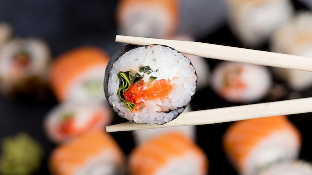 Close-up chopsticks with sushi roll