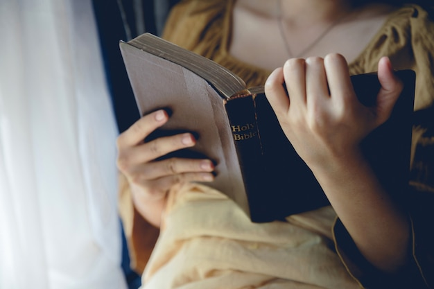 Close-up of a christian woman reading the bible.woman praying on holy bible in the morning.