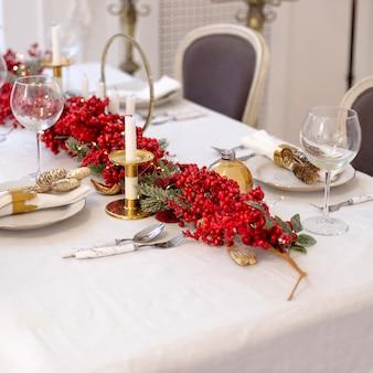 자연과 흰색과 붉은 색으로 크리스마스와 새해 테이블 설정을 닫습니다