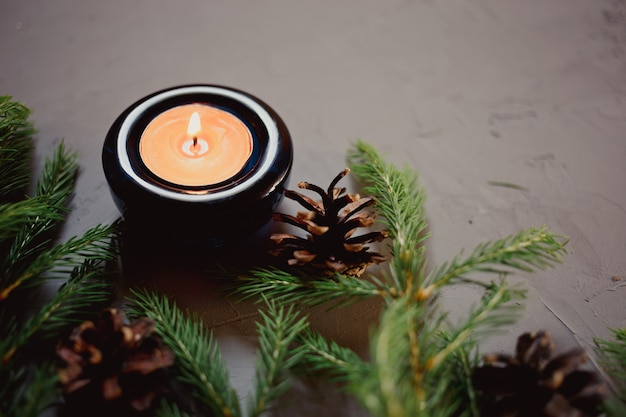 Close up christmas background with fir tree and candle, gray background