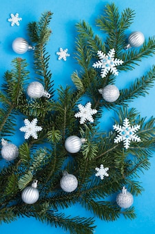 Close-up on christmas composition with spruce branches, silver balls and snowflakes on the blue  background