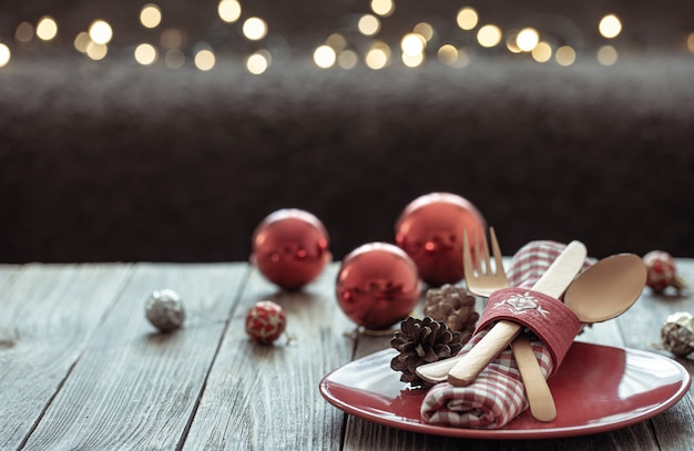 Close up of christmas festive table setting on blurred dark background with bokeh, copy space.