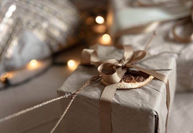 Primo piano di una scatola regalo di natale, decorata con fiori secchi e un'arancia secca, avvolta in carta artigianale.