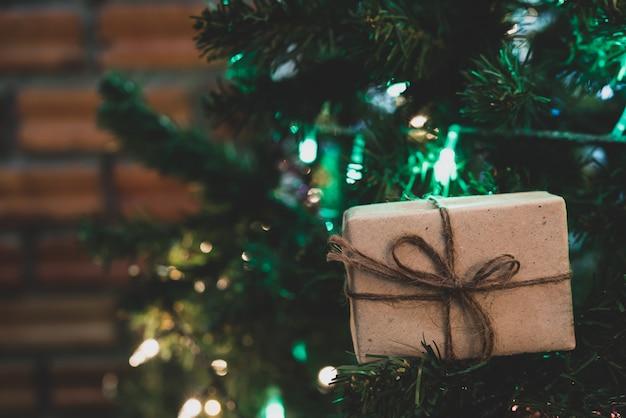 リボンと照明と松の木のクリスマスギフトボックスを閉じる