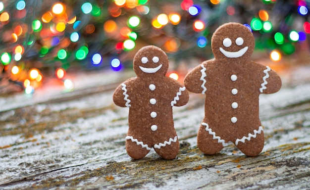 Close-up of christmas gingerbread man family on wooden table with bokeh background