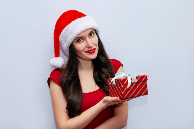 Close up christmas photo of beautiful woman with gift box in red dress and santa hat on grey space.