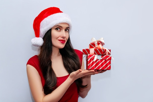 Close up christmas photo of beautiful woman with gift box in red dress and santa hat.